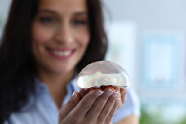 Focus on breast silicone implants in female hands. Happy cheerful brunette looking at transparent breast with gladness. Plastic surgeons and anaplasty concept